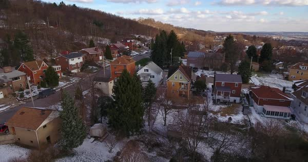 A slowly rising aerial winter view of a typical Western Pennsylvania residential neighborhood.  Royalty-free stock video