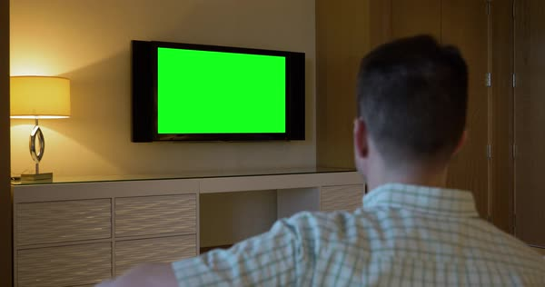 A man watches a television in a luxury hotel room. From behind, with green screen for customizable content.  Royalty-free stock video
