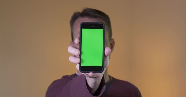 A man holds up a green screen smartphone directly to the camera. With optional corner markers for advanced tracking and screen replacement. Royalty-free stock video