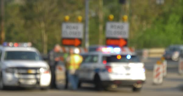 Defocused shot of a closed road with a police car blocking the street as cars pass by. Royalty-free stock video