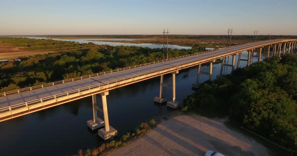 An early morning sunrise forward moving aerial establishing shot of the Topsail Island Bridge over the Intracoastal Waterway as traffic passes over top.  Royalty-free stock video