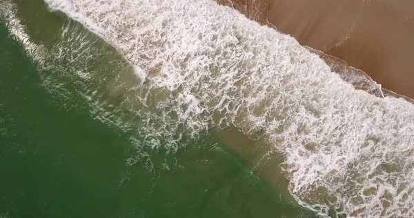 An angled aerial top-down view of the daytime ocean surf hitting against a sandy beach with beachgoers walking along the shoreline. Royalty-free stock video