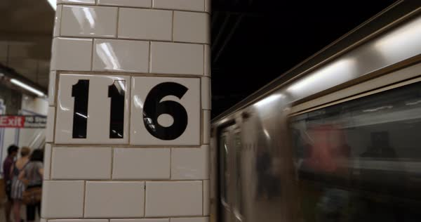 An establishing shot of an MTA Manhattan subway train arriving at the 118th Street station. Royalty-free stock video