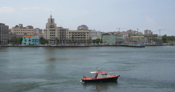 A wide establishing shot of a small pilot boat in the Havana Port Bay. Havana, Cuba skyline is in the background.   Royalty-free stock video