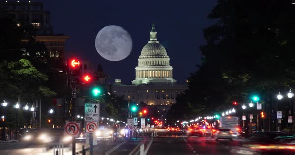 A night timelapse view of traffic activity on Pennsylvania Avenue in Washington, D.C. with the Capitol Dome in the distance. A nearly full moon in the sky.   Royalty-free stock video