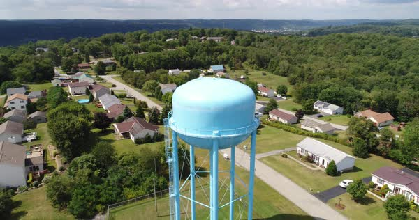 A daytime reverse aerial establishing shot of a typical Pennsylvania residential neighborhood with a large water tower in the foreground. Royalty-free stock video
