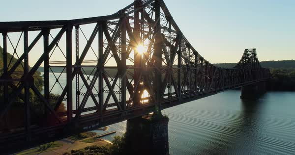 A dramatic rising aerial establishing shot of an old, large railroad bridge over the Ohio River near Monaca, Pennsylvania.  Royalty-free stock video