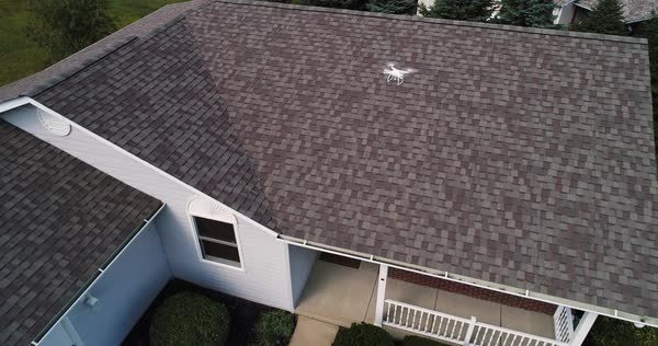 Using a small unmanned drone to safely examine damaged shingles on a residential roof after a storm.   Royalty-free stock video