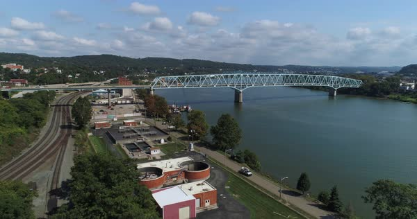 A high angle forward moving aerial establishing shot of the small Western Pennsylvania town of Rochester. The Ohio River is in the distance.   Royalty-free stock video