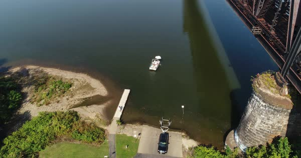 A high angle rising aerial establishing shot of a recreational boat being launched on the Ohio River under a railroad bridge.  Royalty-free stock video