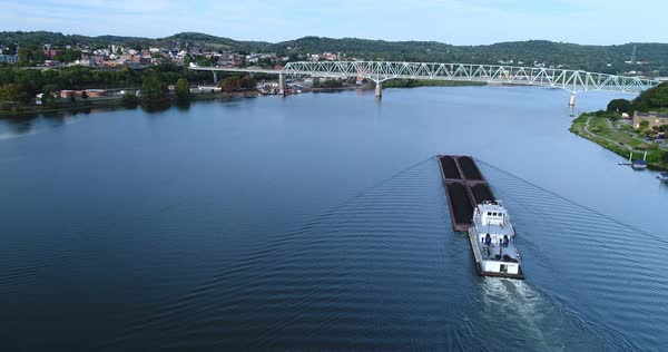 A high wide angle aerial establishing shot of a coal barge traveling on the Ohio River in Western Pennsylvania.   Royalty-free stock video