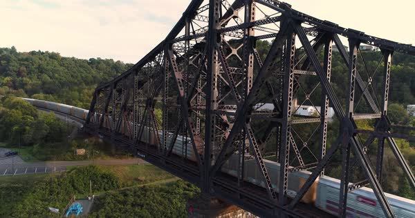 A dynamic rising aerial establishing shot of a cargo trail traveling on a railroad bridge over the Ohio River in Western Pennsylvania.   Royalty-free stock video