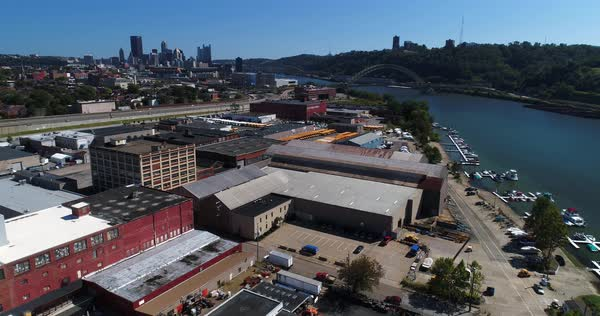 A mid-day slow forward aerial establishing shot of the Pittsburgh skyline with the warehouse business industrial park in the foreground.   Royalty-free stock video