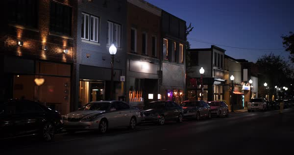 A nighttime establishing shot of businesses on a typical Main Street in America. Pittsburgh suburb. Building names and addresses obscured.  	 Royalty-free stock video