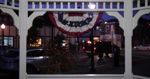 A nitghttime view of a small town street corner and traffic activity as seen through a gazebo.  	 Royalty-free stock video