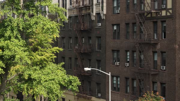 A daytime high angle exterior establishing shot (DX) of typical brick apartment buildings in Manhattan.   Royalty-free stock video