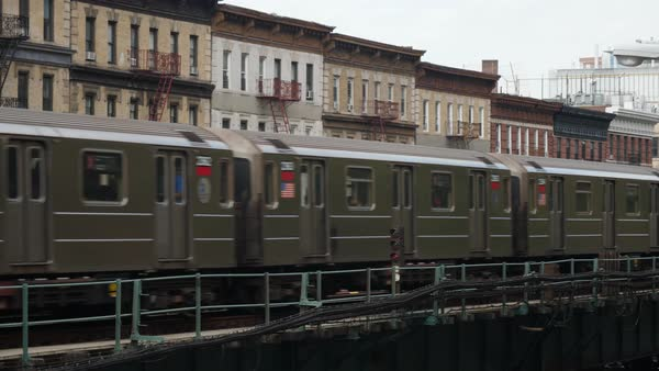 A New York City subway train passes by Harlem apartment buildings on an elevated track.   Royalty-free stock video