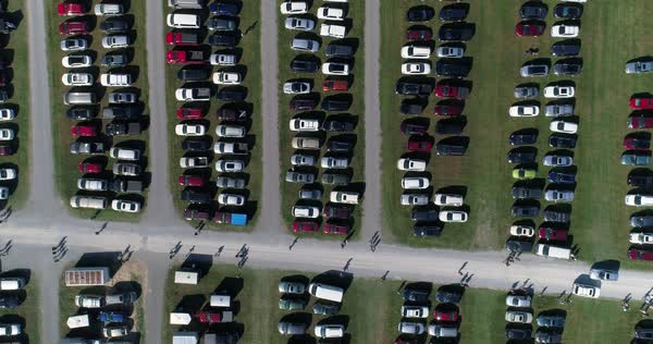 A high view looking straight down on cars and people in a parking lot in an Ohio field outside of a fair.   Royalty-free stock video