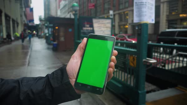 A man holds a green screen smartphone outside of a Manhattan subway entrance on a rainy day. With optional corner pin markers for advanced screen replacement.  Royalty-free stock video