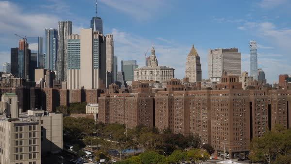 A high angle daytime establishing shot (DX) of the buildings and apartments in Manhattan's Two Bridges neighborhood. The financial district skyline and Freedom Tower in the distance.   Royalty-free stock video