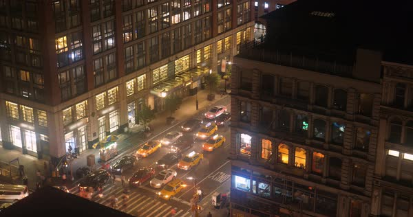 A high angle night timelapse view of people and traffic on a busy Manhattan street and crosswalk.   Royalty-free stock video