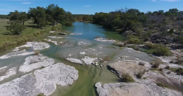 A daytime aerial flyover establishing shot of a creek in Oklahoma.   Royalty-free stock video