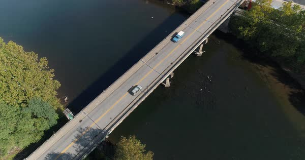 An extreme high angle aerial establishing shot (DX) of light traffic on the Officer McCray Rob Memorial Bridge over the Youghiogheny River. Pittsburgh suburbs.   Royalty-free stock video