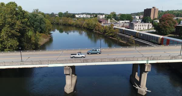A profile aerial view of traffic on the Officer McCray Rob Memorial Bridge over the Youghiogheny River in Connellsville, PA. Pittsburgh suburbs.   Royalty-free stock video