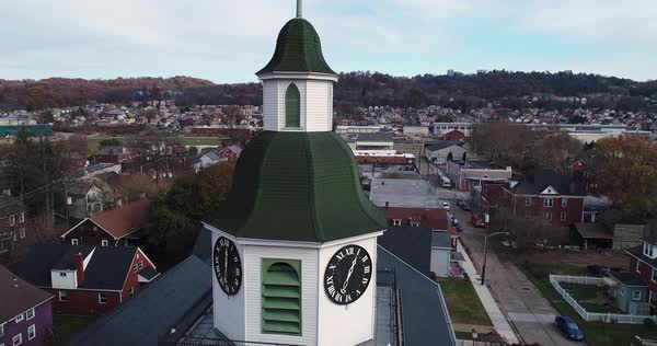 A slow orbit establishing shot around a small town's church steeple on a late Autumn day.   Royalty-free stock video