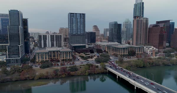 A slow rising reverse aerial establishing shot of Austin, Texas and the Colorado River on an overcast evening.   Royalty-free stock video
