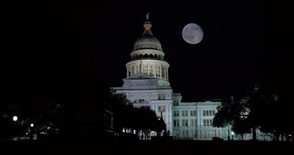 A nighttime side angle view of the Texas state capitol building in downtown Austin, Texas with a partial full moon in the sky Royalty-free stock video