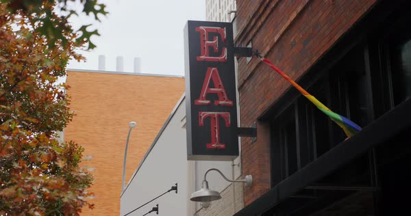 "A daytime view of a red neon ""EAT"" sign on the side of a restaurant in a large city. Royalty-free stock video"