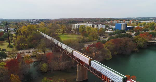 AUSTIN, TX - Circa December, 2017 - A slow forward aerial flyover view of a cargo train traveling over a bridge over the Colorado River in downtown Austin, Texas.   Royalty-free stock video