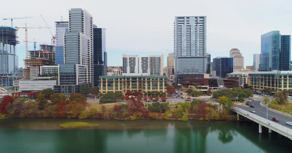 A low profile aerial view of the Austin, Texas skyline with the Colorado River in the foreground. Late Autumn overcast day.   Royalty-free stock video