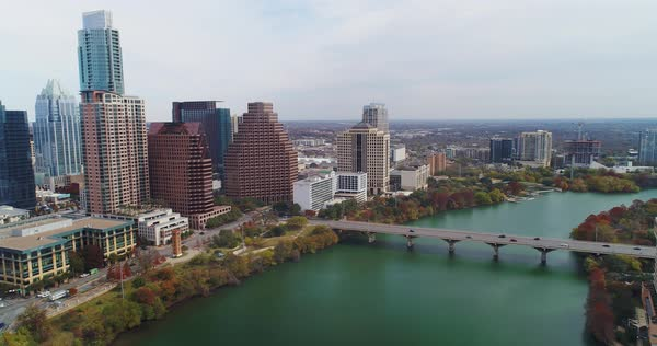 A high angle reverse aerial establishing shot of the Texas, Austin skyline with the Colorado River in the foreground. Late Autumn day with foliage trees.   Royalty-free stock video