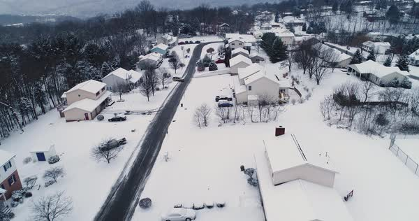 A slow push forward establishing shot of a typical Pennsylvania residential neighborhood after a snow storm. Pittsburgh suburb.   Royalty-free stock video