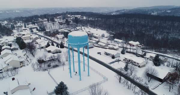 A slowly rising forward aerial establishing shot of a snow covered residential neighborhood in Pennsylvania. Pittsburgh suburb.   Royalty-free stock video