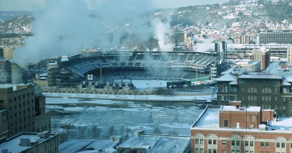 PITTSBURGH, PA - Circa January 2018 - A daytime wintery high angle establishing shot of PNC Park on Pittsburgh's North Shore, home to the Pirates. Ice flows on the frozen Allegheny River.   Royalty-free stock video