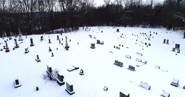 A high forward aerial flyover of snow covered gravestones in an old Pennsylvania countryside cemetery.   Royalty-free stock video
