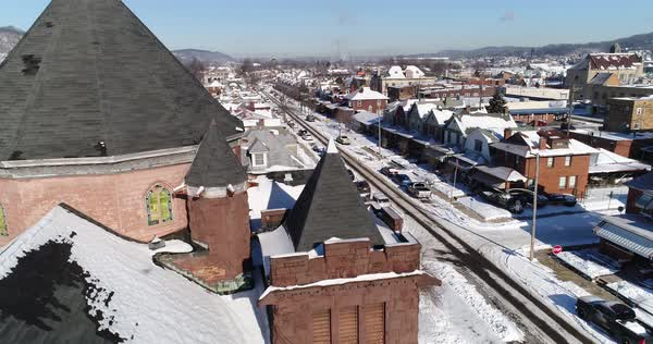 A daytime winter rising aerial establishing shot of a quiet small town's residential neighborhood after a fresh snowfall. Pittsburgh suburbs.   Royalty-free stock video