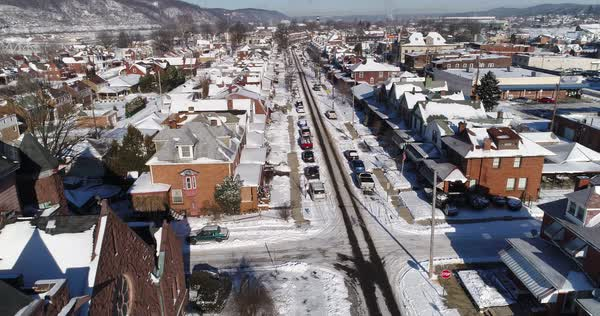 A daytime winter forward aerial establishing shot of a quiet small town's residential neighborhood after a fresh snowfall. Pittsburgh suburbs.   Royalty-free stock video