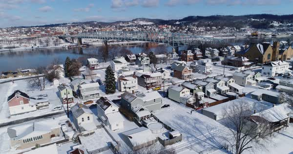 A slow forward winter aerial establishing shot of snow covered roads and houses in a rust belt residential neighborhood. Rochester and Ohio River in the distance. Pittsburgh suburbs.  Royalty-free stock video