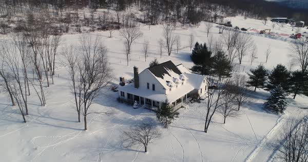 A high angle forward flyover of a typical snow-covered farmhouse in rural Pennsylvania in the winter.   Royalty-free stock video