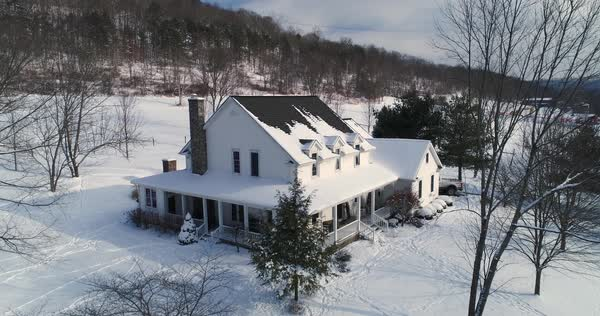 A slow dollying down establishing shot of a typical snow-covered farmhouse in rural Pennsylvania in the winter.   Royalty-free stock video