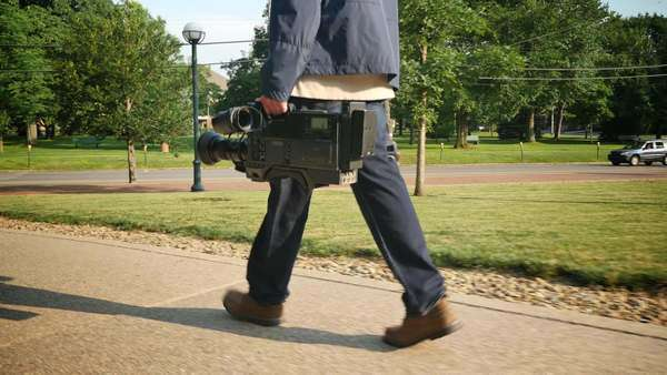 A low angle shot of a cameraman carrying his video camera to a production. Royalty-free stock video