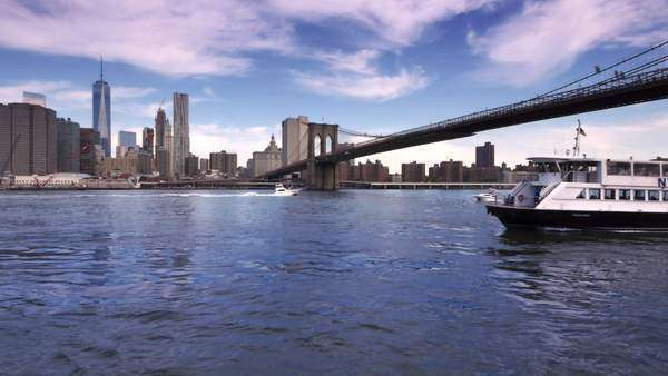 BROOKLYN, NEW YORK CITY - Circa, June, 2015 - An establishing shot of lower Manhattan and the Brooklyn Bridge as seen from Brooklyn as the East River Ferry passes by. Royalty-free stock video