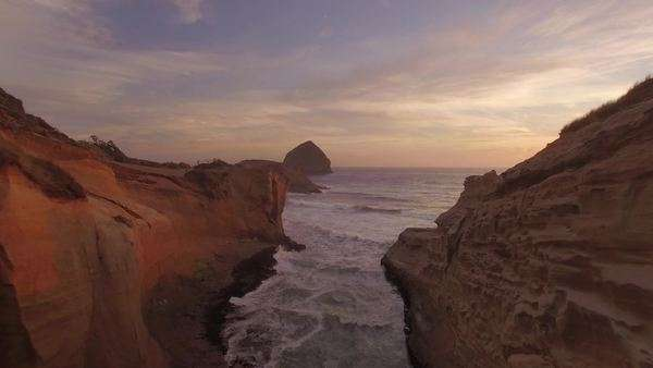 Low aerial shot flying through rock formation along Cape Kiwanda on the Oregon coast. Rights-managed stock video