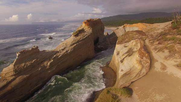 Aerial shot of sea stack and waves along Cape Kiwanda on the Oregon coast. Rights-managed stock video
