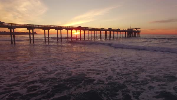 Sunset pier, aerial beach flight Rights-managed stock video