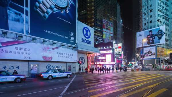 Timelapse pan shot of busy Hong Kong street with people and cars at night. Rights-managed stock video